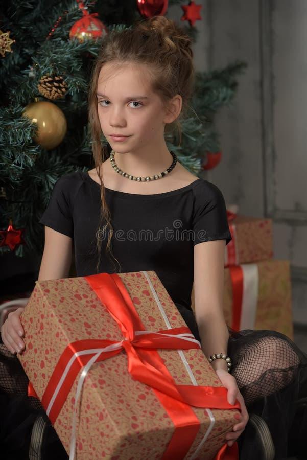 Fille de l'adolescence dans le noir par l'arbre de Noël avec un cadeau photo libre de droits