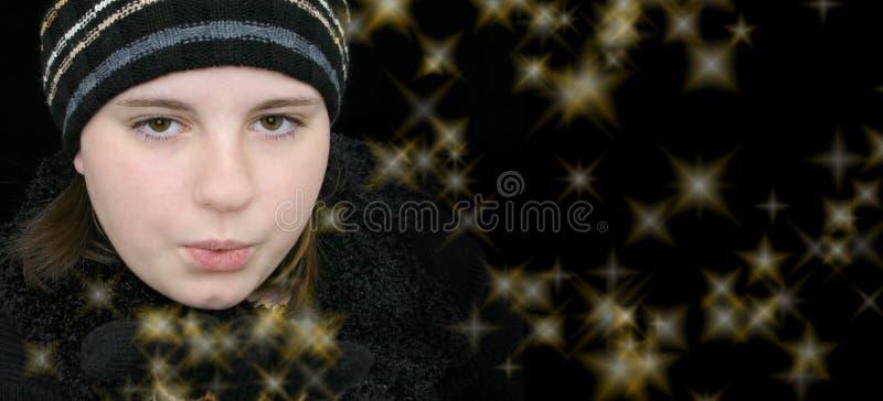 Fille de l'adolescence de l'hiver soufflant les étoiles magiques photo libre de droits
