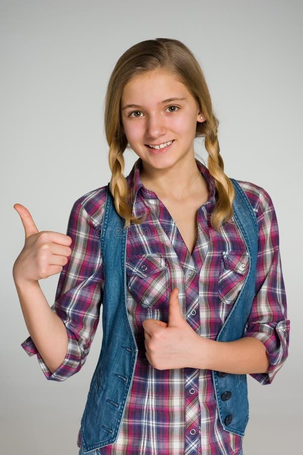 Fille de l'adolescence de sourire avec ses pouces  photographie stock libre de droits