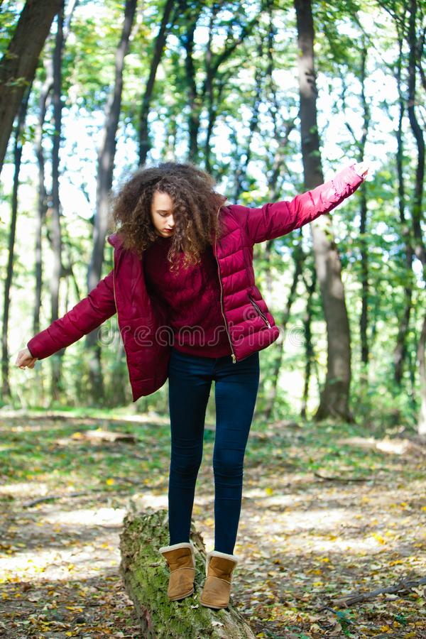 Fille de l'adolescence descendant un tronc tombé dans une forêt d'automne photo stock