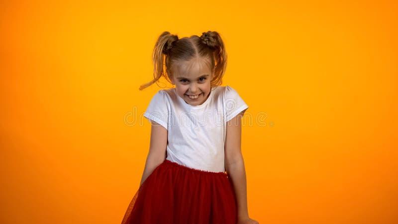 Fille de l'adolescence drôle dans le flirt rouge de jupe, feignant pour être princesse, rêve puéril photos stock