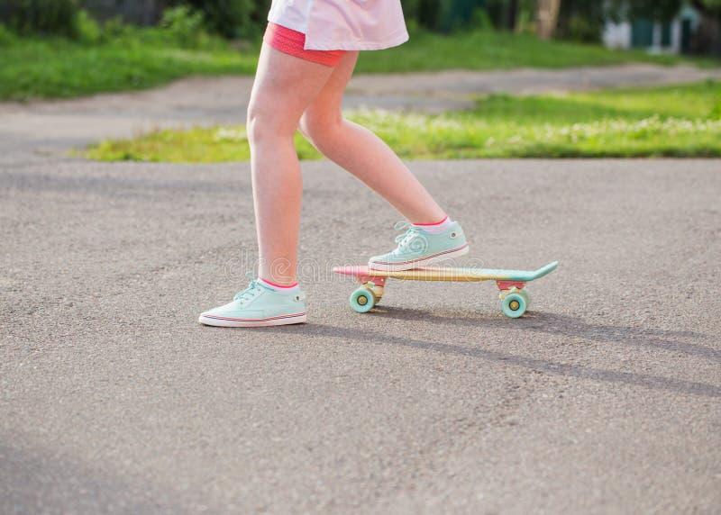 Fille de l'adolescence en bas de la rue avec une planche à roulettes photo stock