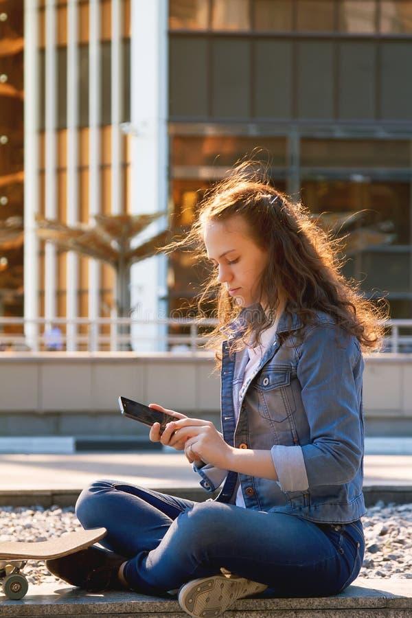 Fille de l'adolescence faisant se reposer un téléphone portable sur un plancher dans une ville image libre de droits