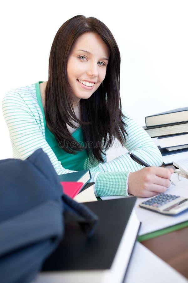 Fille de l'adolescence heureuse étudiant sur un bureau images stock