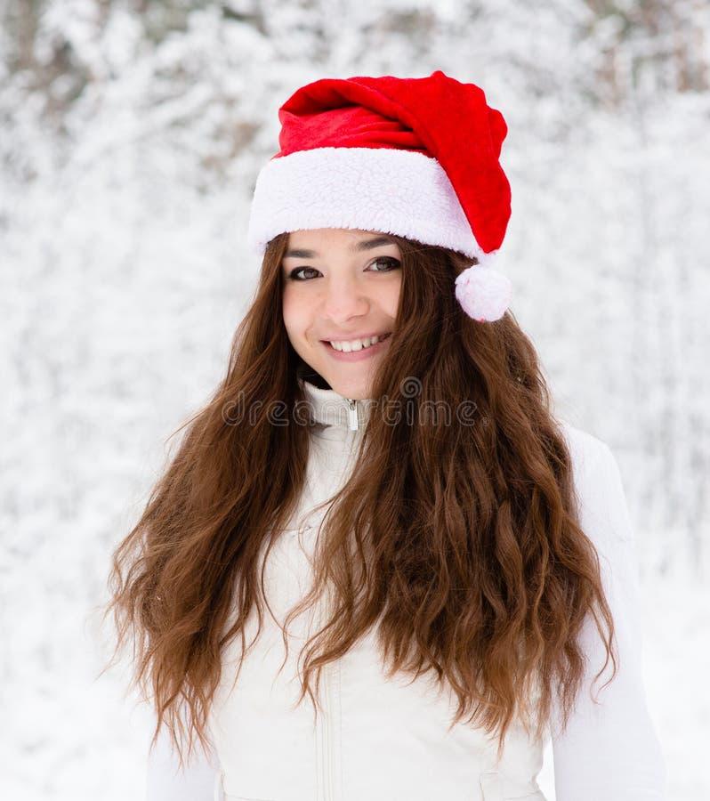 Fille de l'adolescence heureuse avec le chapeau rouge de Santa image stock