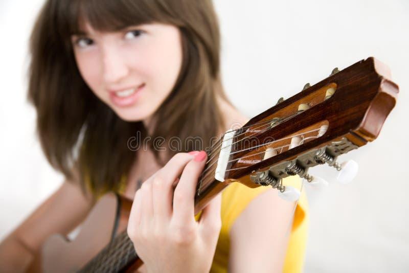 Fille de l'adolescence jouant la guitare images libres de droits