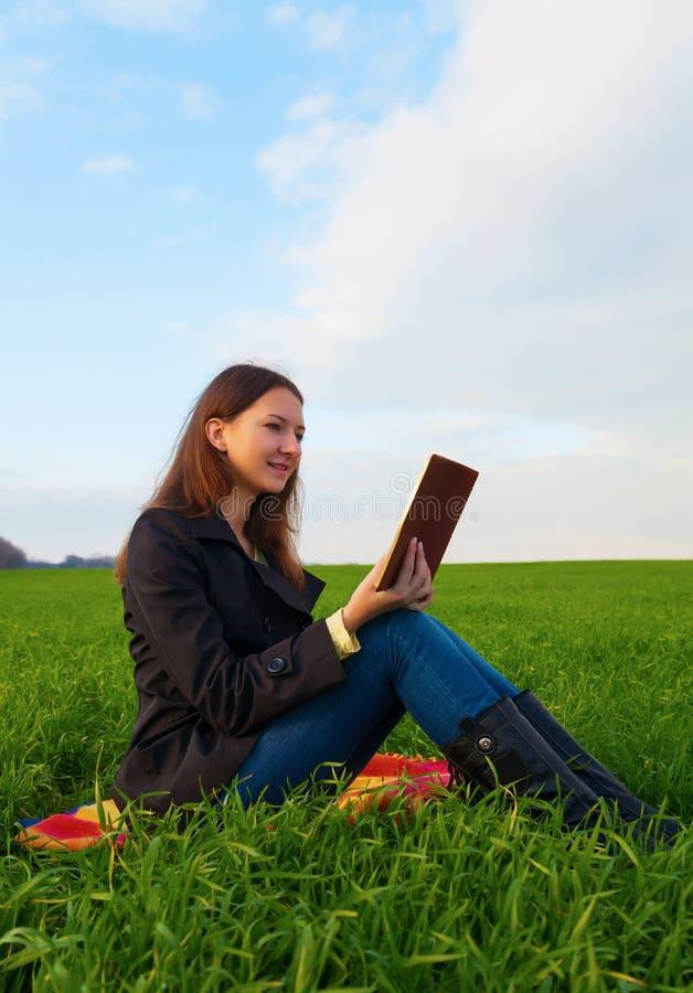 Fille de l'adolescence lisant la bible dehors photographie stock libre de droits