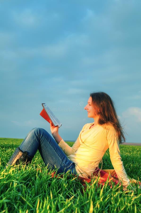 Fille de l'adolescence lisant la bible dehors images stock