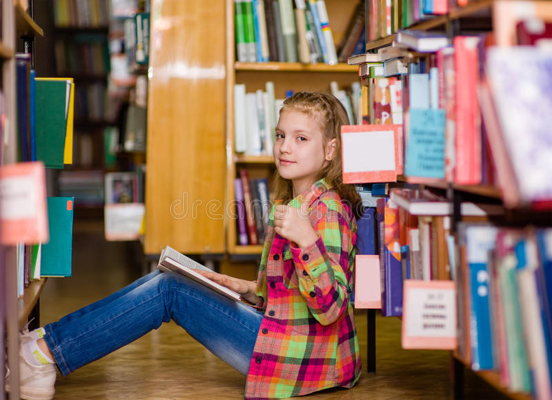 Fille de l'adolescence lisant un livre sur le plancher dans la bibliothèque et montrant des pouces  photo libre de droits