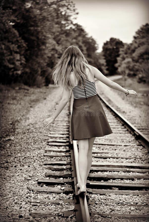 Fille de l'adolescence marchant loin sur une voie de train photos stock