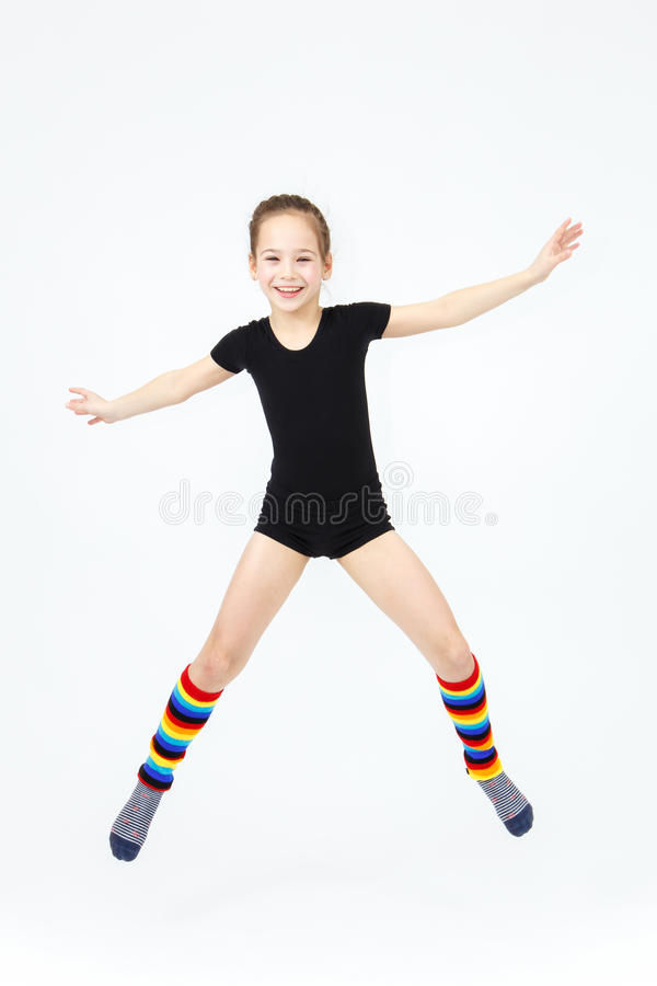 Fille de l'adolescence mince faisant la danse de gymnastique en sautant sur le blanc photographie stock libre de droits