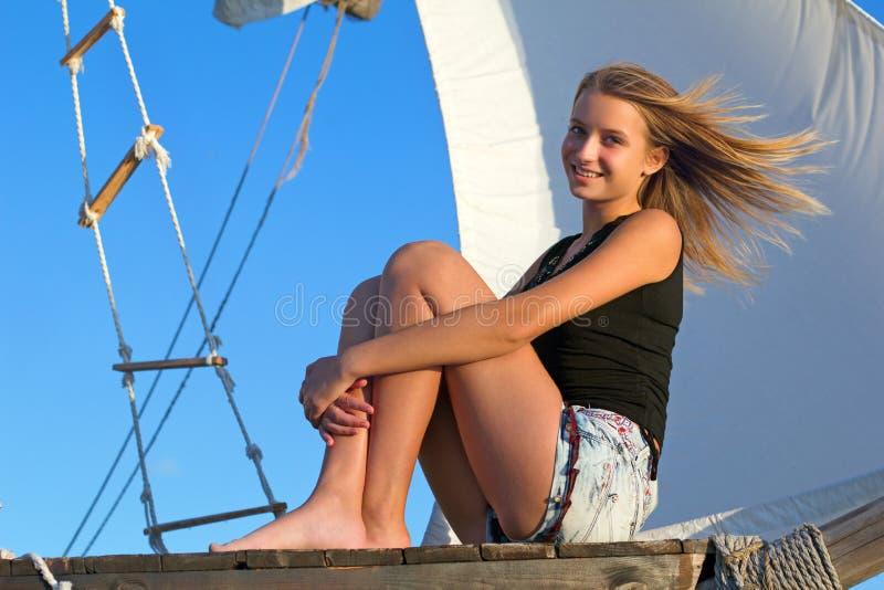 Fille de l'adolescence s'asseyant à la poupe du bateau images libres de droits