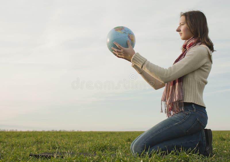 Fille de l'adolescence s'asseyant avec un globe photo libre de droits