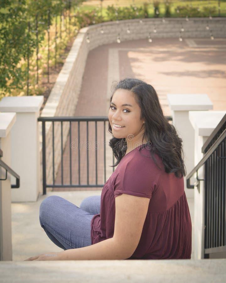 Fille de l'adolescence s'asseyant sur l'escalier photo stock
