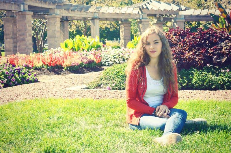 Fille de l'adolescence s'asseyant sur l'herbe avec les fleurs de floraison photographie stock libre de droits