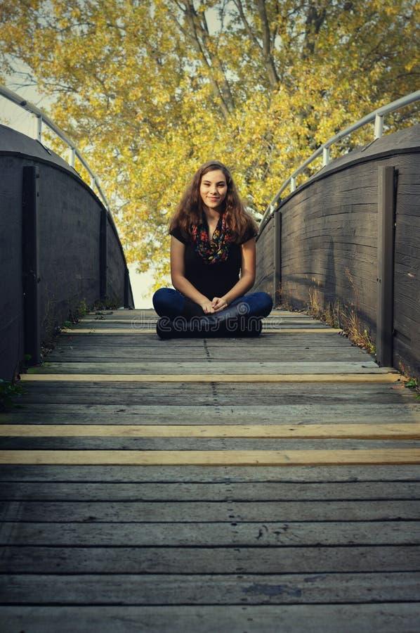 Fille de l'adolescence s'asseyant sur le pont photos stock