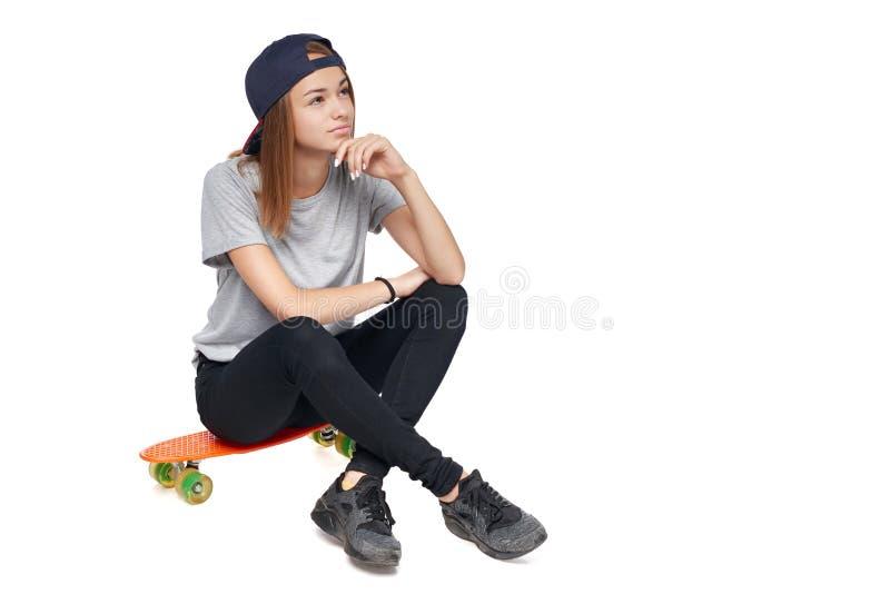 Fille de l'adolescence s'asseyant sur le regard de pensée de panneau de patin au côté photos stock