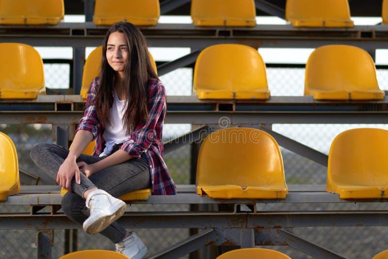 Fille de l'adolescence seule s'asseyant sur des tribunes, photo stock