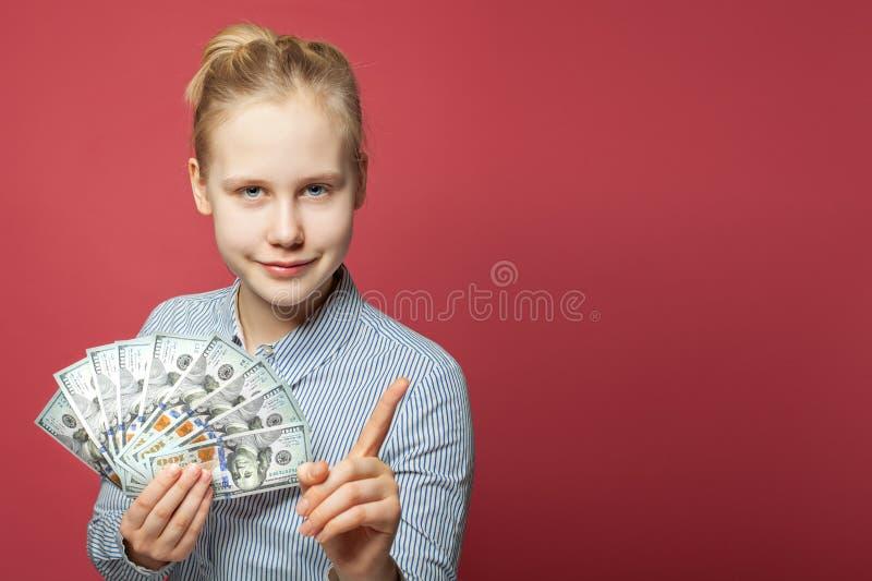 Fille de l'adolescence de sourire heureuse avec l'argent liquide d'argent Concept de ventis, avantageux pour les deux parties et  image libre de droits