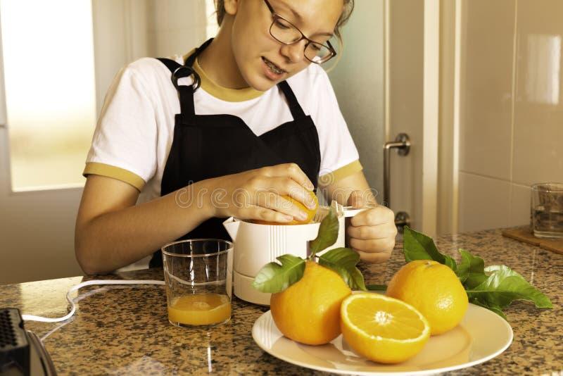 Fille de l'adolescence tenant un presse-fruits d'agrume avec les agrumes oranges et frais dans la cuisine photo stock