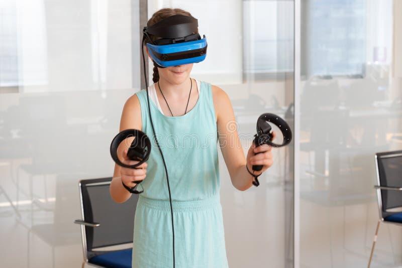 Fille de l'adolescence utilisant le casque de VR, tenant des contrôleurs dans des mains et appréciant une nouvelle expérience photos libres de droits