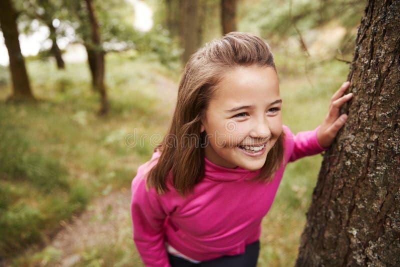 Fille de la préadolescence faisant une pause se penchant sur l'arbre pendant une hausse dans une forêt, vue élevée, fin  image libre de droits