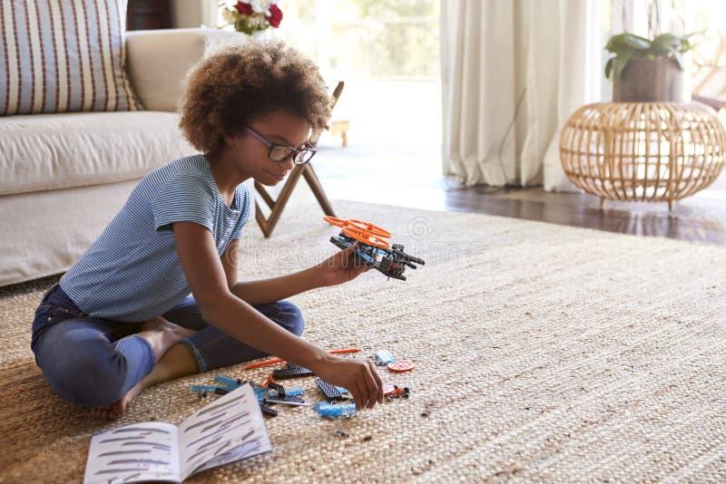 Fille de la préadolescence s'asseyant sur le plancher dans le salon constituant un jouet d'un kit de construction, fin photos libres de droits