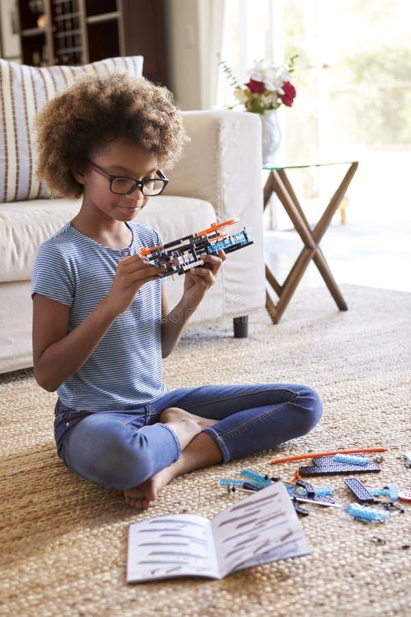 Fille de la préadolescence s'asseyant sur le plancher dans le salon constituant un jouet d'un kit de construction, fin, vertical photo stock