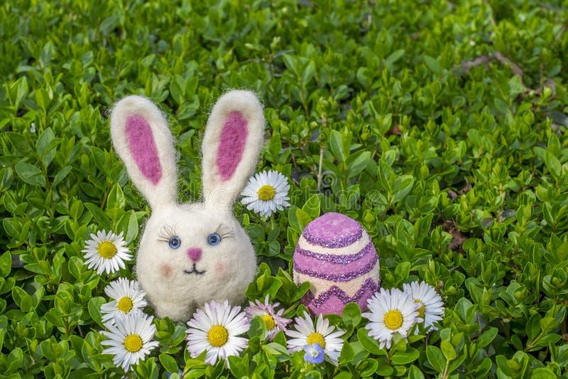 Fille de lapin de Pâques avec l'oeuf et les fleurs de pâques sur le buisson vert images libres de droits