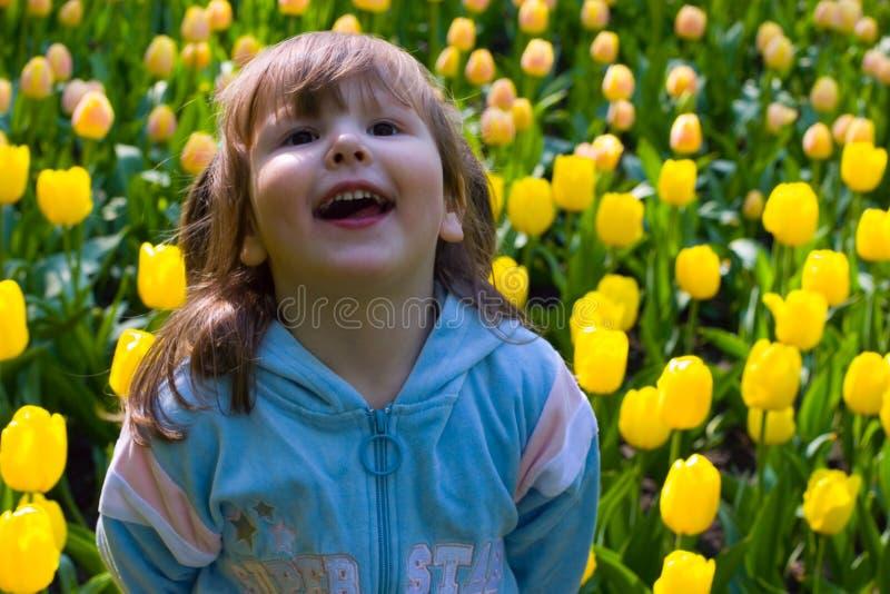 Fille de Laughting dans les tulipes photographie stock libre de droits