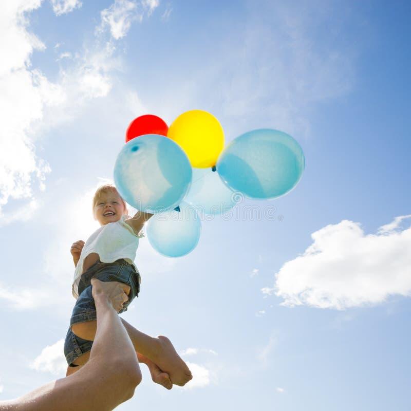 Fille de levage de mère tenant des ballons contre images stock