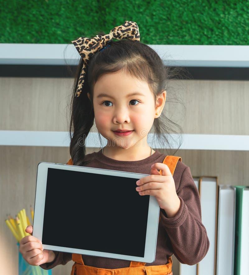 Fille de Littlg tenant la moquerie vide de comprimé dans la salle de classe image libre de droits