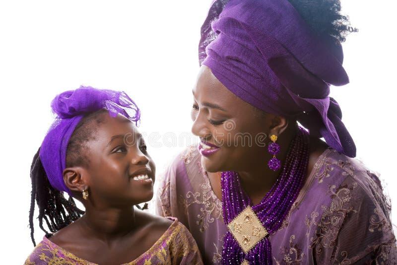 Fille de mère et d'enfant regardant entre eux Habillement traditionnel africain photographie stock