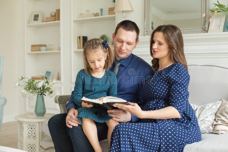 Fille de mère, de père et d'enfant lisant un livre ensemble image libre de droits