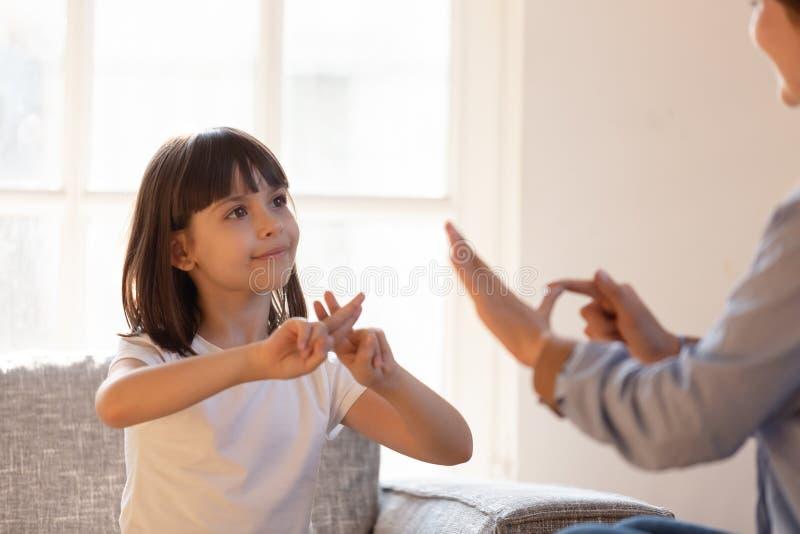 Fille de mère s'asseyant sur la communication non-verbale de divan avec la langue des signes photos stock