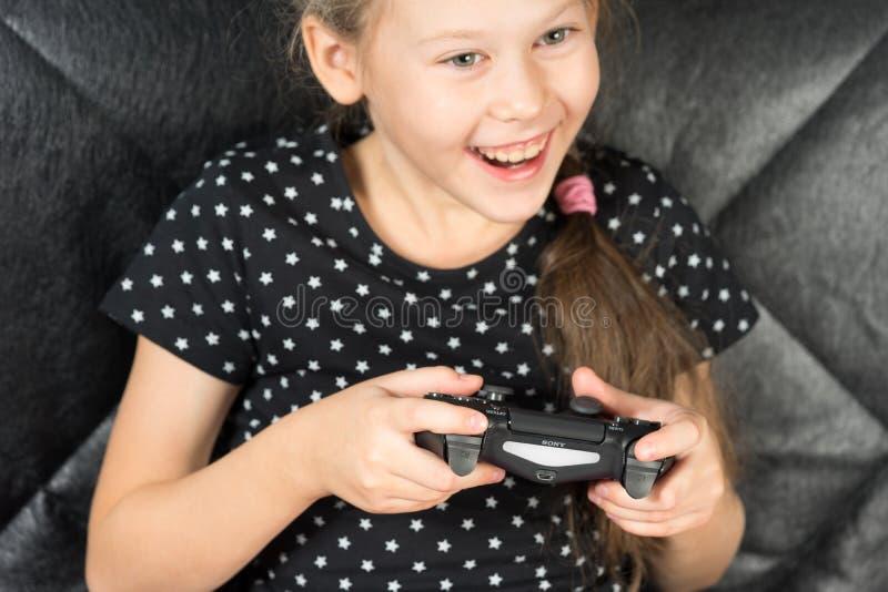 Fille de main jouant Sony Dualshock 4 image stock