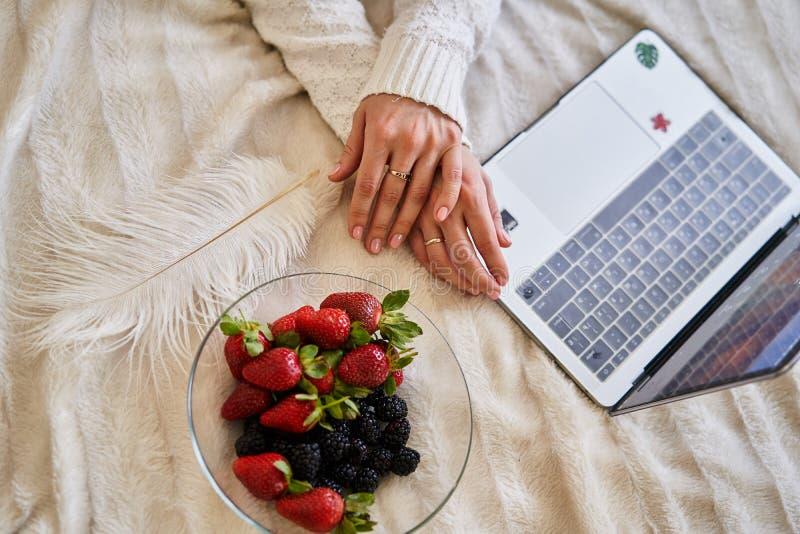 Fille de mains avec un plat des fraises et des mûres dans le lit photographie stock