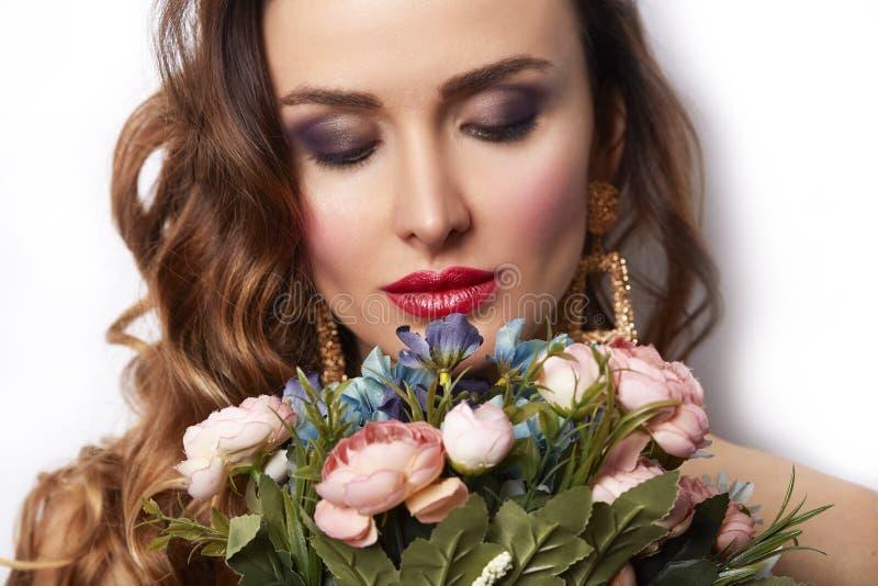 Fille de modèle de beauté avec le bouquet des fleurs Lèvres séduisantes rouges de beau de brune de jeune femme maquillage à la mo photos stock