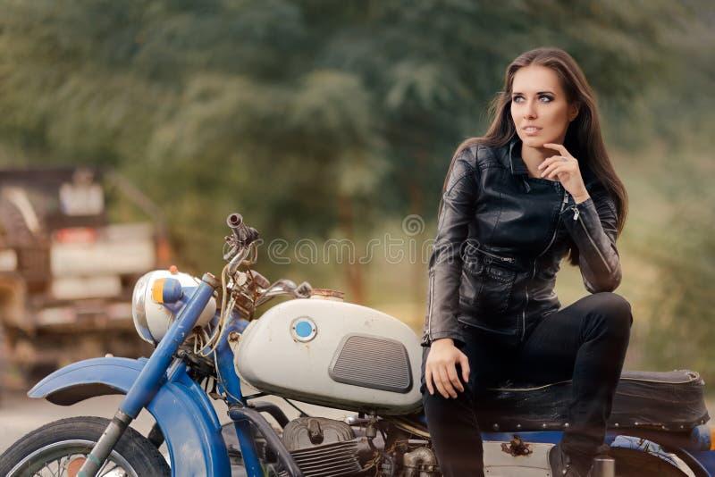 Fille de motard dans la veste en cuir sur la rétro moto photos stock