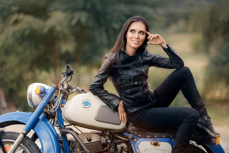 Fille de motard dans la veste en cuir sur la rétro moto image stock