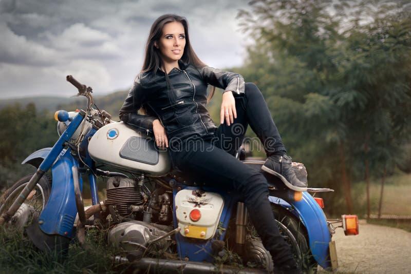 Fille de motard dans la veste en cuir sur la rétro moto photographie stock libre de droits