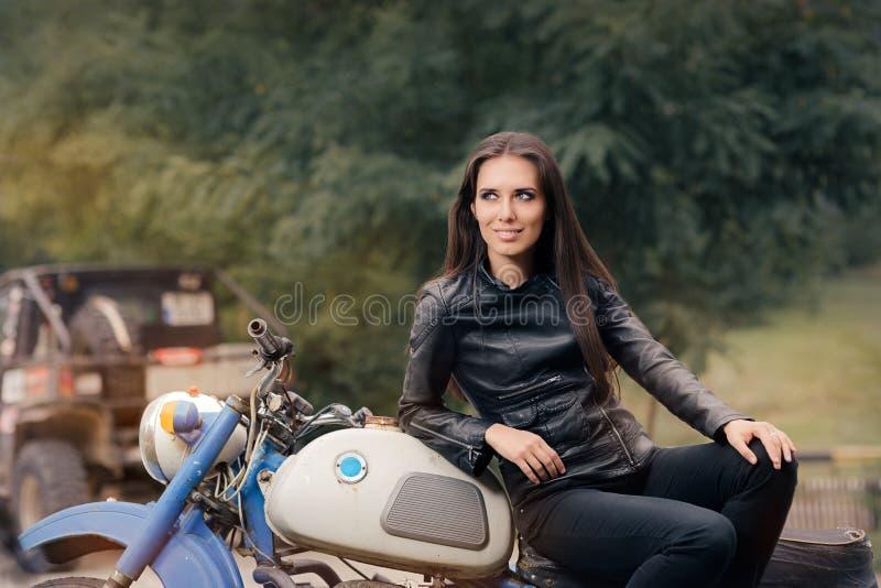 Fille de motard dans la veste en cuir sur la rétro moto photo libre de droits