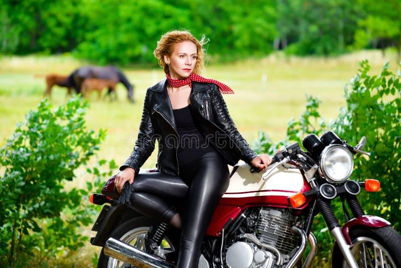 Fille de motard dans la veste en cuir sur une moto image libre de droits
