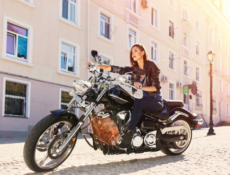 Fille de motard dans une veste en cuir montant une moto image libre de droits