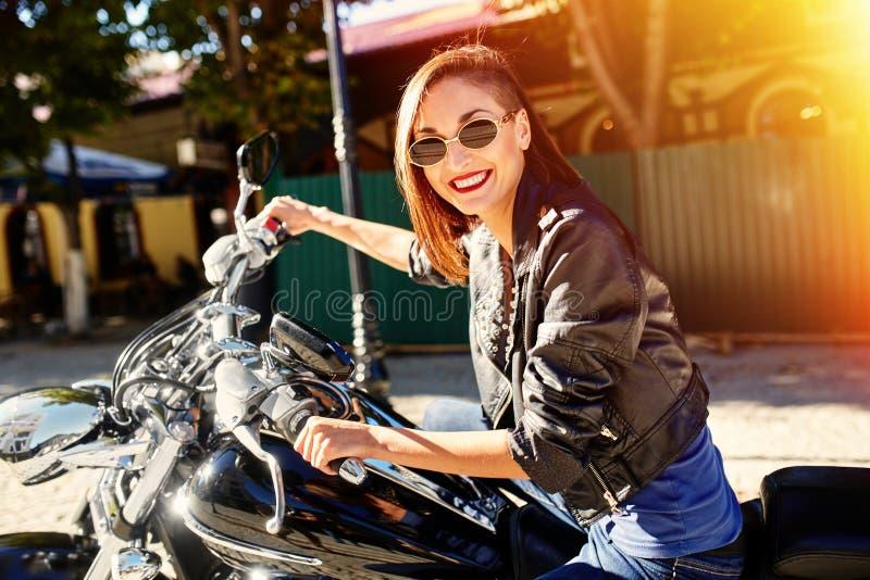 Fille de motard dans une veste en cuir montant une moto photo libre de droits