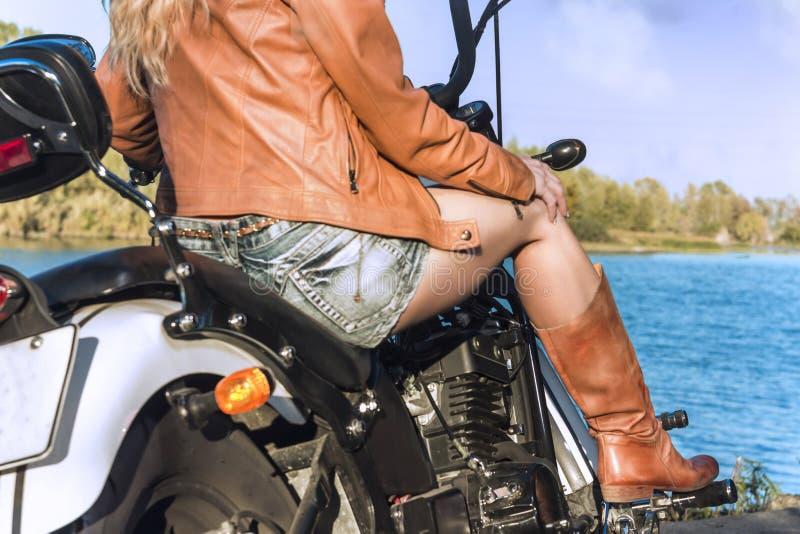 Fille de motard dans une veste en cuir sur la moto près de la rivière images libres de droits