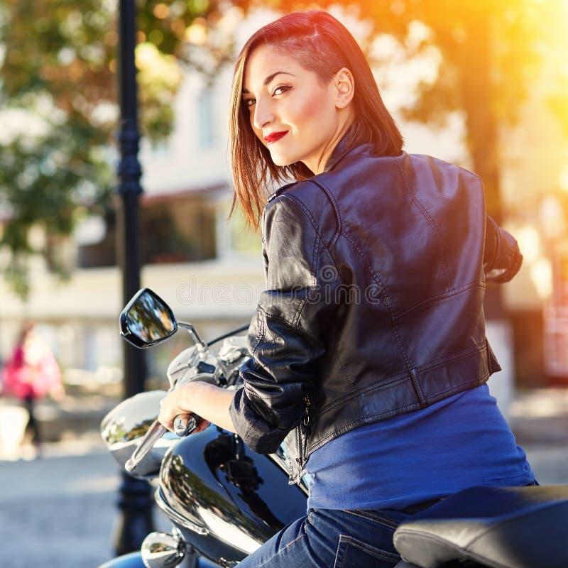 Fille de motard dans une veste en cuir sur une moto photographie stock libre de droits