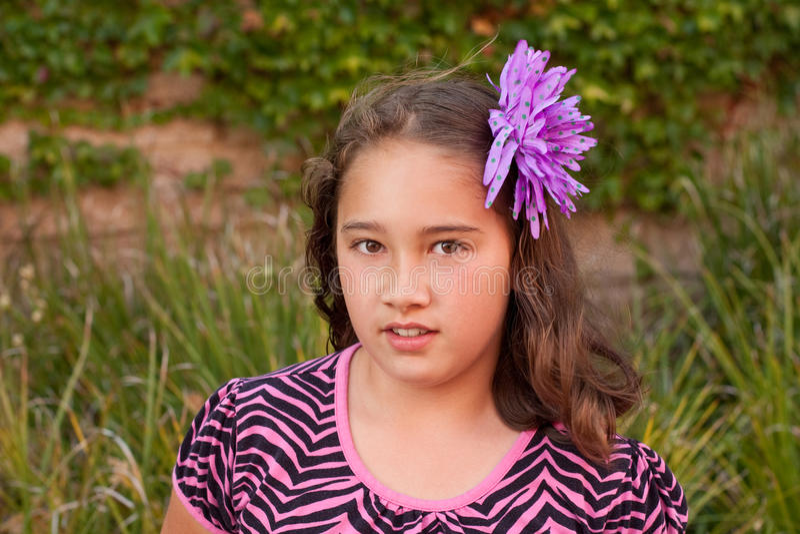 Fille de neuf ans avec la fleur dans le cheveu photos stock
