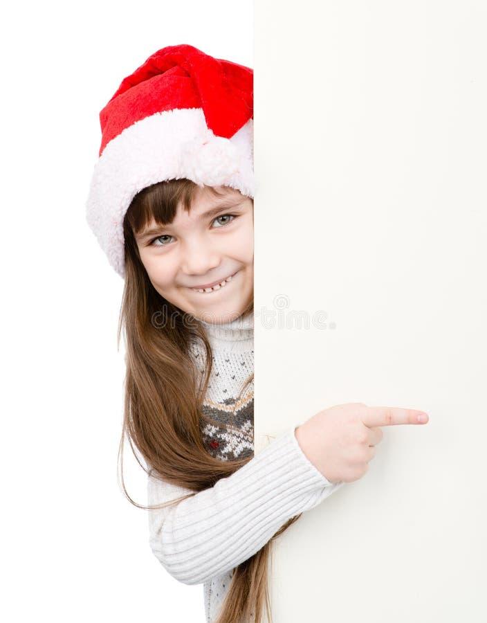 Fille de Noël dans le chapeau d'aide de Santa se dirigeant sur le conseil blanc vide D'isolement sur le blanc image stock