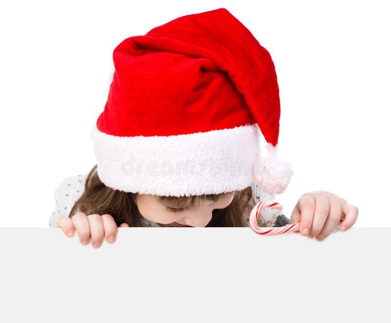 Fille de Noël heureux avec le chapeau de Santa derrière le conseil blanc regardant vers le bas D'isolement sur le fond blanc photos stock